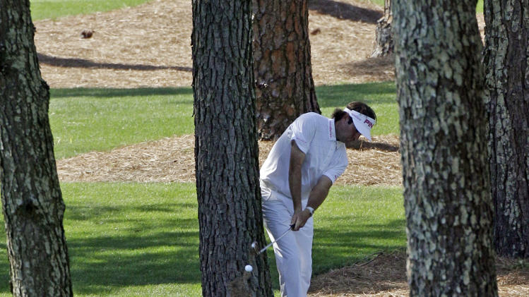 Bubba Watson hits out of the trees off the seventh fairway during the fourth round of the Masters golf tournament Sunday, April 8, 2012, in Augusta, Ga. (AP Photo/Matt Slocum)