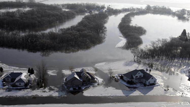 In this March 28, 2009 file photo, homes are surrounded by floating ice and floodwater as the Red River continues to rise in Fargo, N.D. Federal Emergency Management Agency officials are frustrated by the number of people in the Red River Valley and elsewhere in North Dakota who don't have flood insurance, citing the state's history of presidential disaster declarations. The number of insurance policies in flood-prone Fargo and Cass County, where residents have battled flooding along the Red River and its tributaries for six of the last eight years, dropped by more than 40 percent from 2011 to 2012, FEMA officials said. (AP Photo/Carolyn Kaster)
