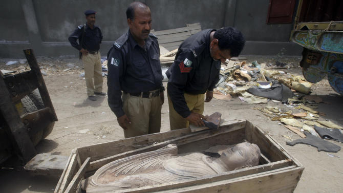 In this Friday, July 6, 2012 photo, Pakistani police officers examine an ancient Buddhist sculpture seized by police Friday, that smugglers were attempting to spirit out of the country, in Karachi, Pakistan. Pakistani officials say police have seized many sculptures of Buddha and other related religious figures worth millions of dollars that experts indicated could be over 2,000 years old. (AP Photo/Shakil Adil)
