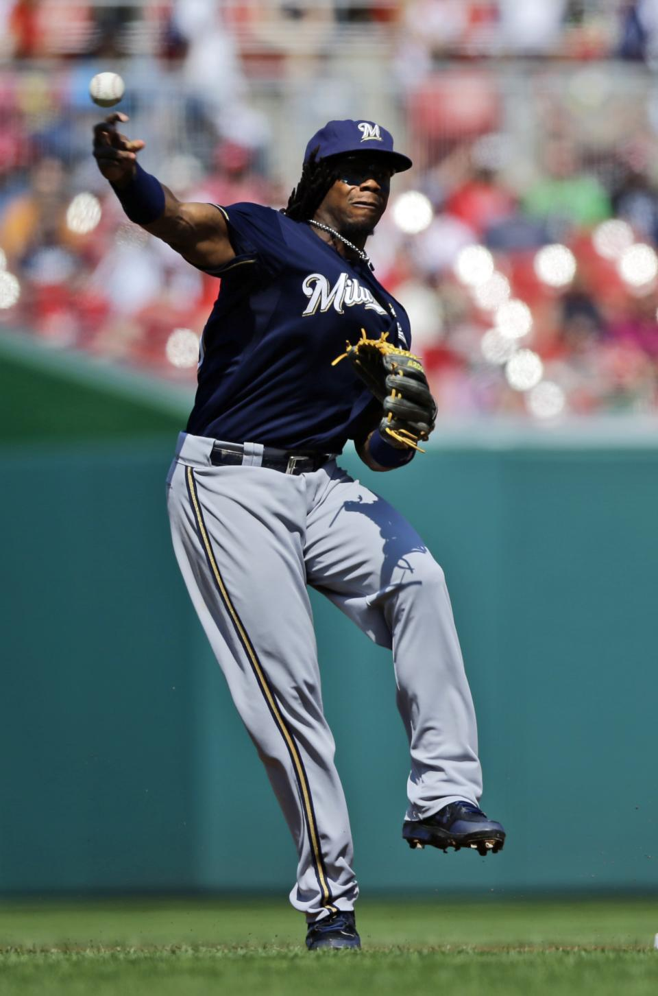Milwaukee Brewers second baseman Rickie Weeks throws to first but not in time as Washington Nationals' Ryan Zimmerman is safe during the first inning of a baseball game at Nationals Park Saturday, Sept. 22, 2012, in Washington.  (AP Photo/Alex Brandon)