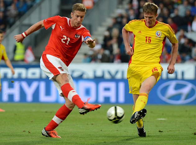 Austria's  Marc Janko (L) And Romania's Nicolai Dorin Goian  Vie For The Ball AFP/Getty Images
