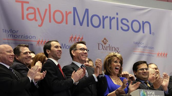 Sheryl Palmer, President and CEO of Taylor Morrison, joined by members of the company's management team, applauds during opening bell ceremonies of the New York Stock Exchange, as they celebrate the company's IPO, Wednesday, April 10, 2013. Stocks are opening higher on Wall Street, a day after the Dow Jones industrial average closed at its second all-time high in a week. (AP Photo/Richard Drew)