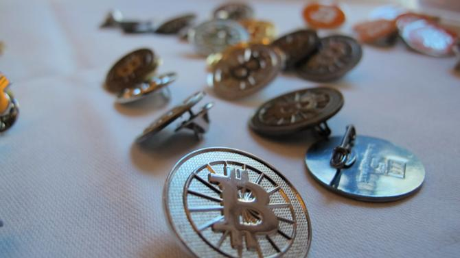 Bitcoin buttons are displayed on a table at the Inside Bitcoins conference in Berlin on Wednesday, Feb. 12, 2014. The conference brought together entrepreneurs and enthusiasts of the virtual currency to discuss business opportunities and recent developments. (AP Photo/Frank Jordans)