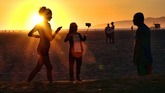 "In this Friday, March 27, 2015 photo, a beachgoer using a cell phone on a stick snaps a selfie as the sun sets at Venice beach in Los Angeles. You can bring your beach towels and floral headbands, but forget that selfie stick if you're going to the Coachella or Lollapalooza music festivals. The sticks are banned this year at the events in Indio, California, and Chicago. Coachella dismissed them as ""narsisstics"" on a list of prohibited items. (AP Photo/Richard Vogel)"
