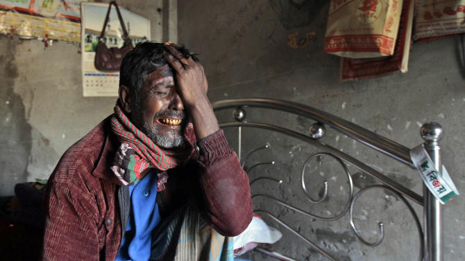 In this Wednesday, Jan. 23, 2013 photo, Bangladeshi man Ansar, who uses one name, reacts at his home near the gutted Tazreen factory on the outskirts of Dhaka, Bangladesh. Two months after his wife and daughter were killed in a fire at the Bangladeshi garment factory, 55-year-old Ansar is scrambling to survive. Ansar has been unable to pay his rent for two months and fears that if he gets evicted and is forced to return to his home village in the impoverished north, he may never be compensated. The fire drew international attention to the conditions that garment workers toil under in Bangladesh, where the $20 billion-a-year textile industry is incredibly powerful and politically connected. (AP Photo/A.M.Ahad)
