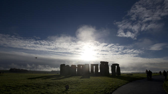Visitors take photographs of the world heritage site of Stonehenge, England, Tuesday, Dec. 17, 2013. It has been standing for thousands of years, so Britain's ancient Stonehenge monument was due a makeover. The 27 million pound ($44 million) renovation which was previewed Tuesday includes a new building 1.5 miles (2.4 kilometers) from the stones where the 1 million a year visitors can watch an exhibition about Neolithic life. (AP Photo/Alastair Grant)