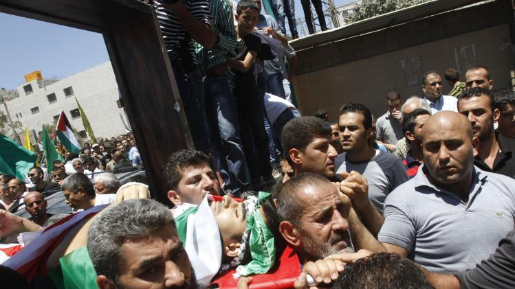Palestinians carry the body Khaled Azmi, whom medics said was killed during clashes with Israeli troops on Friday, during his funeral in the West Bank town of Hawara near Nablus