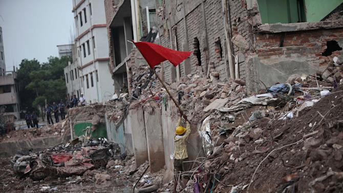 A Bangladeshi rescue worker puts a red flag, marking the end of rescue operations at the site where a Bangladesh garment-factory building collapsed on April 24 in Savar, near Dhaka, Bangladesh, Monday, May 13, 2013. Nearly three weeks after the building collapsed, the search for the dead ended Monday at the site of the worst disaster in the history of the global garment industry.(AP Photo/A.M. Ahad)
