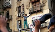 An Egyptian boy waves his shoes as he joins supporters of the Muslim Brotherhood in a protest in Cairo&#39;s Tahrir Square. Egypt&#39;s top court on Thursday paved the way for the ruling military to assume parliament&#39;s powers by annulling the Islamist-led house while allowing Hosni Mubarak&#39;s last premier to stand in this weekend&#39;s presidential election