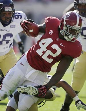 Alabama running back Eddie Lacy (42) runs through the defense of Western Carolina defensive lineman Eric Banford (96) during the first half of an NCAA college football game at Bryant-Denny Stadium in Tuscaloosa, Ala., Saturday, Nov. 17, 2012. (AP Photo/Dave Martin)
