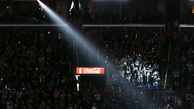 The Los Angeles Kings watch as the Stanley Cup championship banner is raised before the Kings' NHL hockey game against the Chicago Blackhawks in Los Angeles, Saturday, Jan. 19, 2013. (AP Photo/Jae C. Hong)