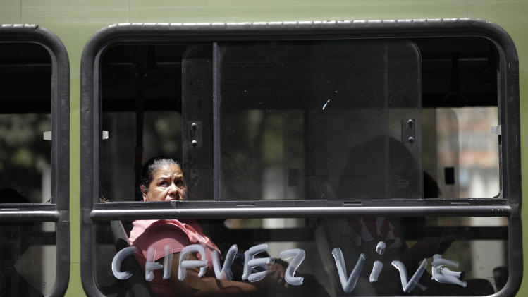 "A woman peers through a bus window that is covered in the Spanish words: ""Chavez is alive"" near the military hospital where President Hugo Chavez is allegedly receiving treatment in Caracas, Venezuela, Wednesday, Feb. 20, 2013. Chavez's sudden return to Venezuela after more than two months of cancer treatments in Cuba has fanned speculation that the president could be preparing to relinquish power and make way for a successor and a new election. (AP Photo/Ariana Cubillos)"