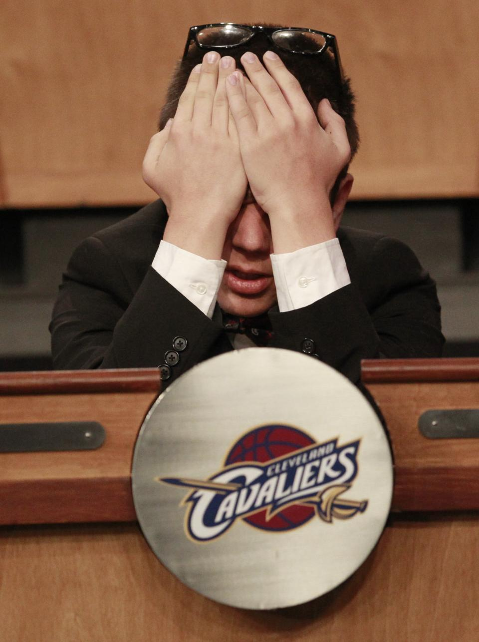 Nick Gilbert, 14, the son of Cleveland Cavaliers owner Dan Gilbert, covers his face prior to the start of the 2011 NBA basketball draft lottery, Tuesday, May 17, 2011 in Secaucus, N.J. Gilbert represented the Cavaliers, who won the lottery. (AP Photo/Julio Cortez)