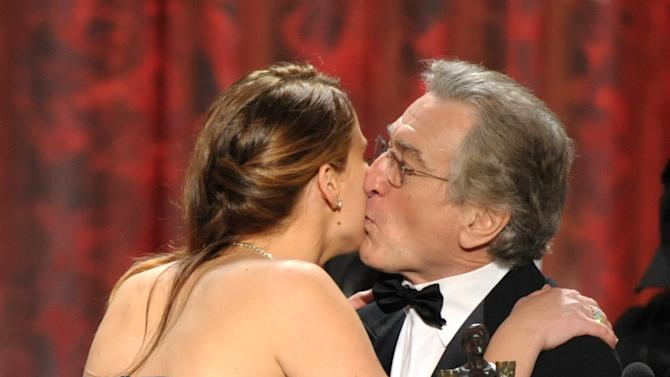 """Jennifer Lawrence, left, and Robert De Niro kiss as she accepts the award for outstanding female actor in a leading role for """"Silver Linings Playbook"""" at the 19th Annual Screen Actors Guild Awards at the Shrine Auditorium in Los Angeles on Sunday Jan. 27, 2013. (Photo by John Shearer/Invision/AP)"""