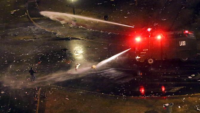 Riot police use water cannons to disperse to Chile's soccer fans during clashes after Chile's victory over Peru in their Copa America 2015 semi-finals soccer match in Santiago