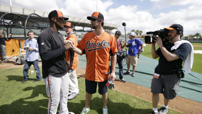 Former Olympic swimmer Michael Phelps talks with Baltimore Orioles center fielder Adam Jones, left, during a baseball spring training workout Thursday, Feb. 21, 2013, in Sarasota, Fla.  Phelps, a native of Baltimore who was in the area filming his Golf Channel show The Haney Project, took batting practice with the team. (AP Photo/Charlie Neibergall)