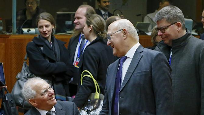 German Finance Minister Wolfgang Schaeuble talks with his French counterpart Michel Sapin during a European Union finance ministers meeting in Brussels