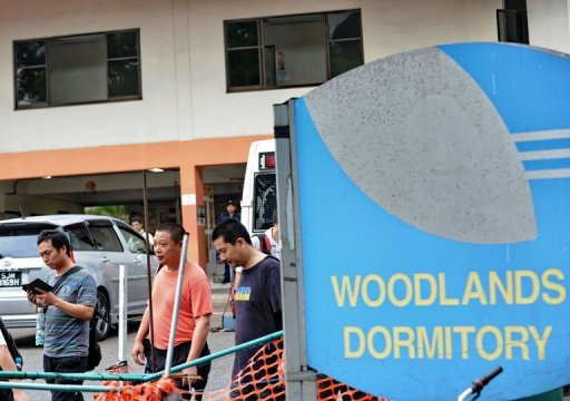Foreign workers walk out of their dormitory in Singapore. Singapore Tuesday issued a warning to mainland Chinese bus drivers, who are staging the first strike in the city-state for more than 25 years, an act that could land them in prison