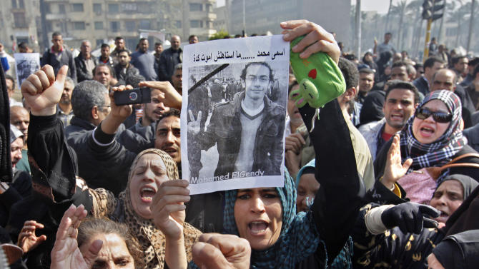 "Egyptian relatives of Mohammed el-Gindy, a 28-year-old activist, who died early Monday of wounds sustained during clashes last Friday near the presidential palace, display his picture as they shout anti-president Morsi slogans during his funeral procession in Tahrir Square, Cairo, Egypt, Monday, Feb. 4, 2013. More than 60 people have died in recent protests across Egypt that began on Thursday, Jan. 24, 2013, the eve of the second anniversary of the start of the uprising that toppled autocrat Hosni Mubarak. Arabic reads ""my name is Mohammed and I did not deserve to die this way."" (AP Photo/Amr Nabil)"