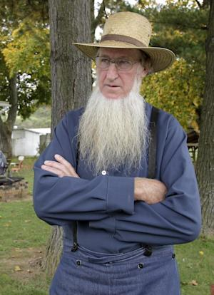 FILE - In an Oct. 10. 2011 file photo, Sam Mullet Sr., the leader of a breakaway Amish group, stands in the front yard of his Bergholz, Ohio home. Mullet and 15 other Amish men and women are to go on trial Monday, Aug. 27, 2012, in Cleveland on charges of carrying out hate crimes in the hair-cutting attacks. Other charges include conspiracy, evidence tampering and obstruction of justice in what prosecutors say are crimes motivated by religious differences. They could face lengthy prison terms if convicted.( AP Photo/Amy Sancetta, File)