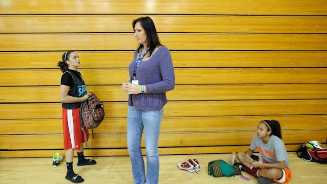 Gabrielle Ludwig, a 6-foot-6-inch transsexual player on Mission College's women's basketball squad, speaks with teammate Felicia Anderson, left, after practice on Friday, Dec. 7, 2012, in Santa Clara, Calif. Gabrielle Ludwig made sports history this month as a basketball player at a Northern California community college. The 50-year-old transsexual, Army veteran, father and Mission College freshman is believed to be the first hoopster to play college ball as both a man and a woman.  (AP Photo/Noah Berger)