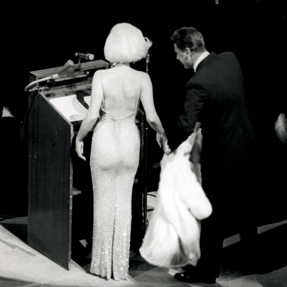 "In this May 19, 1962 publicity photo provided by Running Press, Peter Lawford, right, tends to Marilyn Monroe's fur as she prepares to sing ""Happy Birthday"" to President John F. Kennedy at a Madison Square Garden gala in New York. (AP Photo/Courtesy Running Press)"