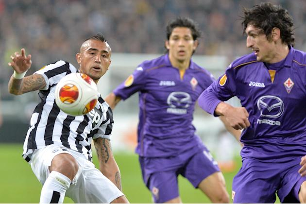 Juventus midfielder Arturo Vidal, left, of Chile, challenges for the ball with Fiorentina defender Stefan Savic, right, during an Europa League, round of 16, soccer match between Juventus and Fiorenti