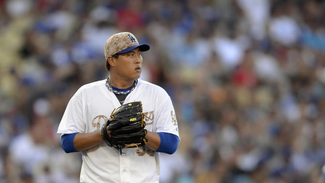 Los Angeles Dodgers starting pitcher Hyun-Jin Ryu checks the scoreboard after his second strikeout in the seventh inning of a baseball game against the Cincinnati Reds, Monday, May 26, 2014, in Los Angeles. (AP Photo/Gus Ruelas)