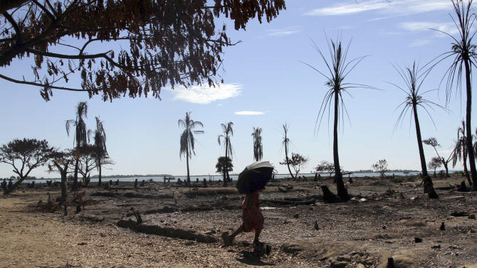 In this photo taken on Nov. 7, 2012, a woman walks through the ruins caused by the recent violences in Pauk Taw, Sittwe, Rakhine state, western Myanmar. In the west, terrified villagers fled burning homes in an explosion of ethnic and religious violence. In the north, refugees from a civil war cower in chilly camps, desperately short on life's basic necessities. And in dank jails, hundreds of political prisoners languish behind bars, wondering when they'll ever be freed.  This is Myanmar, the country hailed by the West for its stunning democratic transformation since last year. It still has reams of unfinished business, little of which will be seen by President Barack Obama when he becomes the first American head of state to visit the country's pagoda-studded main city on Monday, Nov. 19, 2012. (AP Photo/Khin Maung Win)