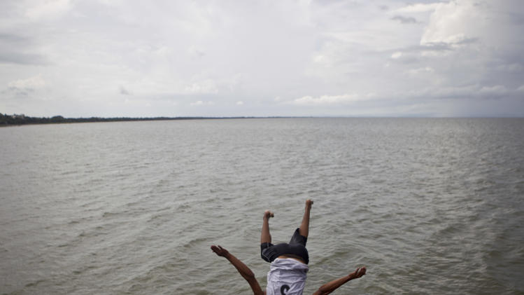 A youth jumps from the wharf into Cocibolca Lake, also known as Nicaragua Lake, in Granada, Nicaragua, Friday, June 7, 2013. A concession to build a canal across Nicaragua linking the Pacific Ocean and Caribbean Sea, which would go through the waters of Lake Nicaragua, will be awarded to a Chinese company, the National Assembly president said Wednesday. (AP Photo/Esteban Felix)