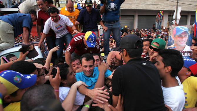 Opposition presidential candidate Henrique Capriles, center, is hugged by supporters while trying to climb a fence during a campaign rally in Maracay, Venezuela, Thursday, April 4, 2013. Venezuela will hold a presidential election to replace late President Hugo Chavez on April 14. (AP Photo/Fernando Llano)