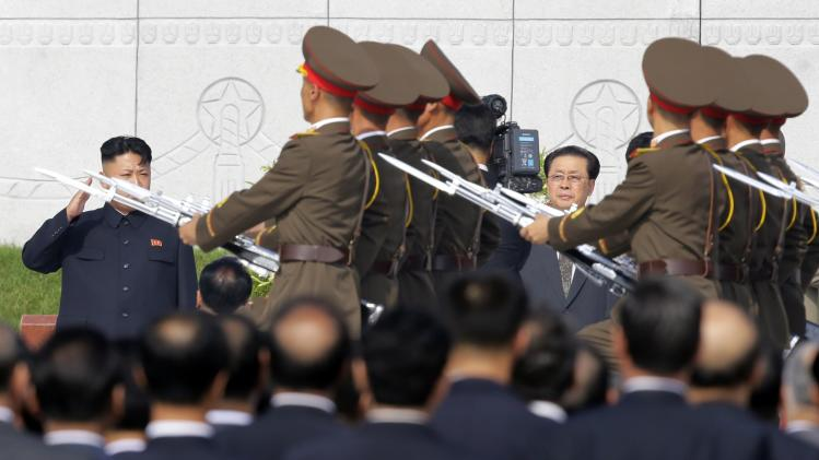 File photo of Kim Jong Un saluting to the members of the honour guards as he and Jang Song Thaek attend a commemoration event in Pyongyang