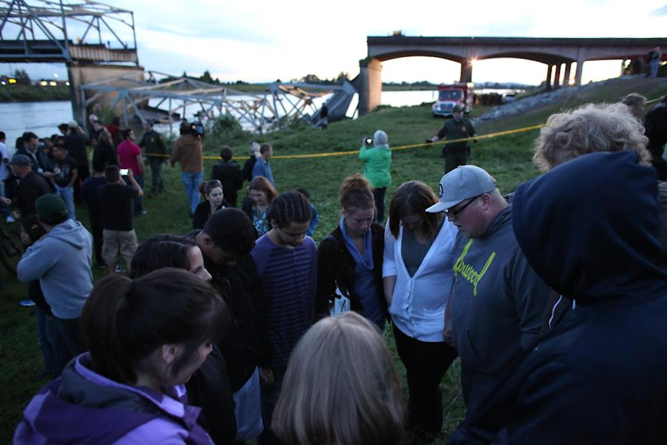 People offer spontaneous prayer after an Interstate 5 bridge collapsed over the Skagit River between Mt. Vernon and Burlington, Wash. on Thursday, May 23, 2013. Two cars and one travel trailer went in the water. There were no know fatalities. (AP Photo/seattlepi.com, Joshua Trujillo)