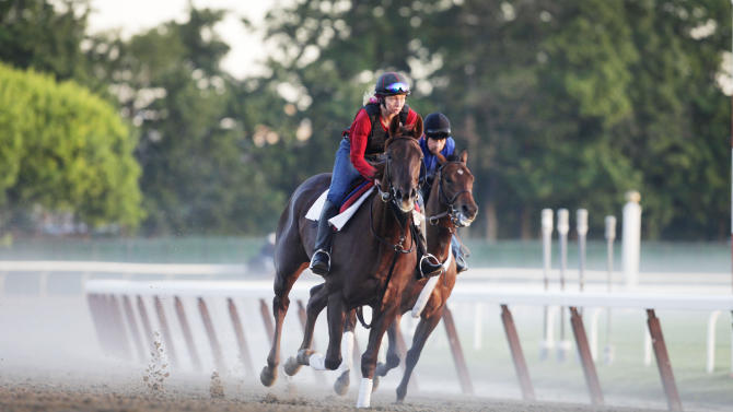 Horses run through a morning fog as they round the fourth and final turn during training at Belmont Park, Wednesday, June 6, 2012 in Elmont, N.Y. The Belmont Stakes horse race is Saturday. (AP Photo/Mark Lennihan)
