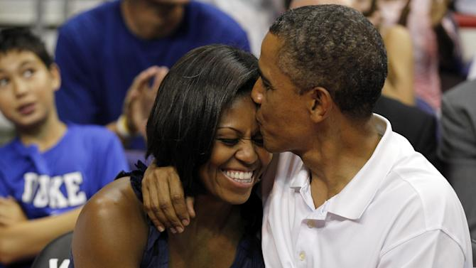"""President Barack Obama kisses the head of first lady Michelle Obama, left, after kissing her for """"Kiss Cam"""" in the second half while attending the Olympic men's exhibition basketball game between Team USA and Brazil, Monday, July 16, 2012, in Washington. Team USA won 80-69. (AP Photo/Alex Brandon)"""