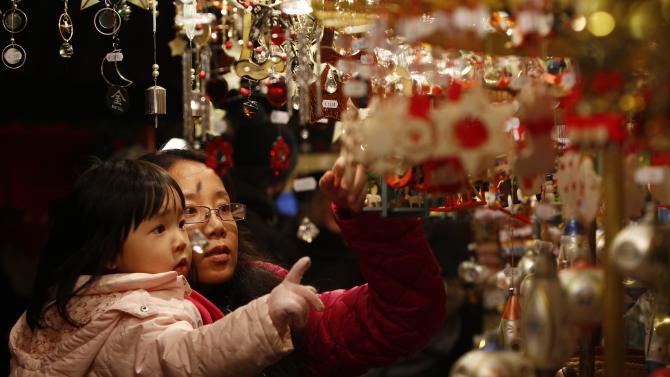 People look at Christmas decorations at opening day of Germany's oldest Christkindlesmarkt in Nuremberg