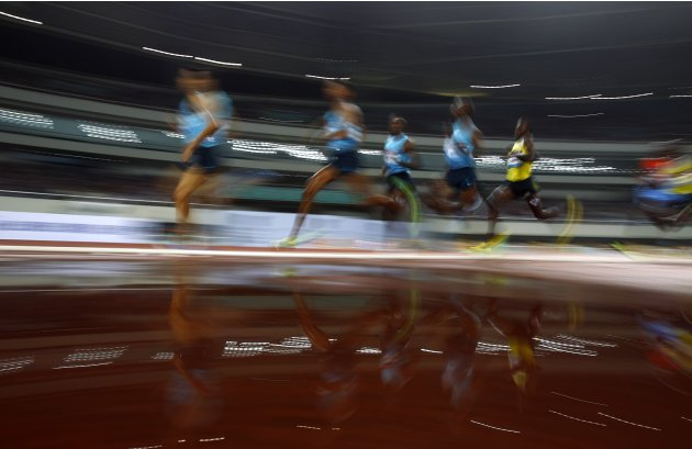 Athletes are reflected in a puddle of water during the men's 1500m at the IAAF Diamond League Athletics meet in Shanghai
