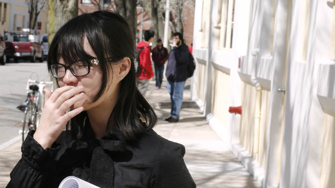 A Boston University student who knew Boston Marathon bombing victim Lu Lingzi pauses while talking about her friend outside the Boston University School of Mathematics and Statistics in Boston Wednesday, April 17, 2013. (AP Photo/Winslow Townson)