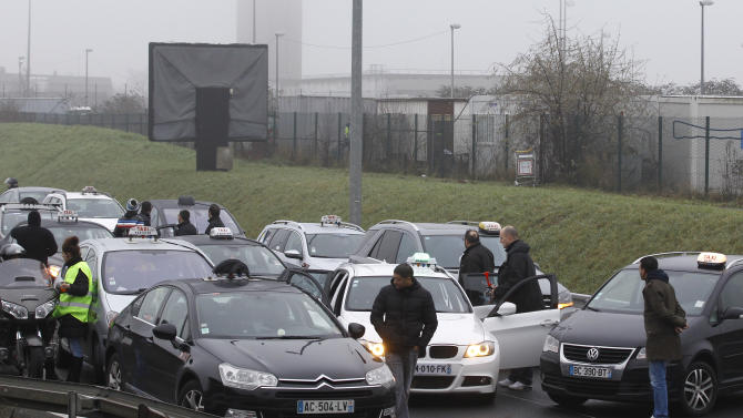 Taxi drivers stop the traffic on the highway leading to Paris, Thursday, Jan. 10, 2013 at Roissy airport. Taxi drivers across France were putting on the brakes to clog traffic, slow access to airports and force would-be passengers to find alternate transport in a strike over government efforts to deregulate the transportation industry. (AP Photo/Remy de la Mauviniere)