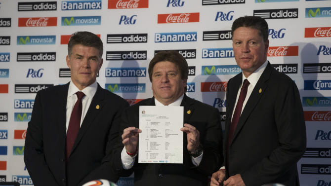 Mexican soccer team head coach Miguel Herrera, center, holds up the list of players selected for Mexico's 2014 Brazil World Cup team, as he poses for a picture with Director of National Selection Hector Gonzalez, left, athletic director Ricardo Pelaez, at a press conference to announce the World Cup lineup, in Mexico City, Friday, May 9, 2014. (AP Photo/Rebecca Blackwell)