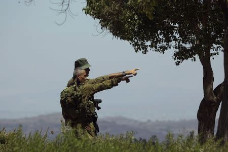 Israeli soldiers observe the Syrian side of the Quneitra border crossing between the Israeli-controlled Golan Heights and Syria.
