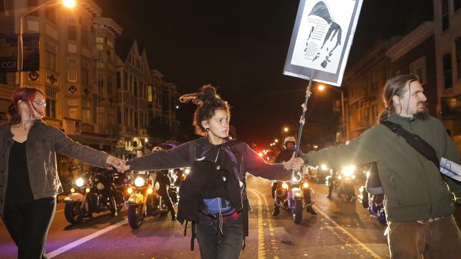 Protesters hold hands to slow down advancing police officers on motorcycles during a demonstration against the grand jury's decision in the Ferguson shooting of Michael Brown, in San Francisco