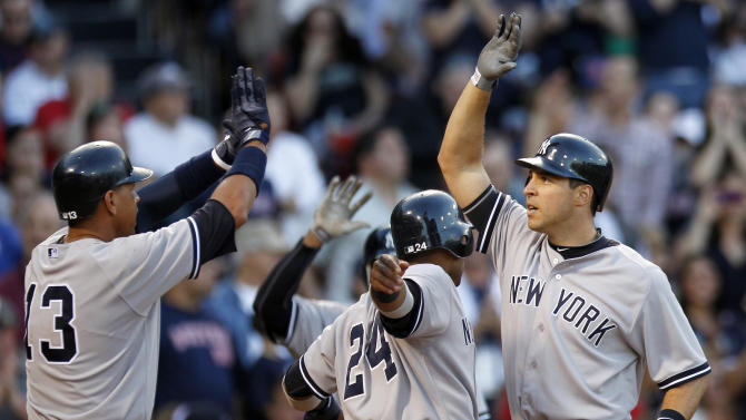 New York Yankees' Mark Teixeira, right, celebrates his three-run home run that drove in Alex Rodriguez (13) and Robinson Cano (24) in the seventh inning of a baseball game against the Boston Red Sox in Boston, Saturday, April 21, 2012. (AP Photo/Michael Dwyer)