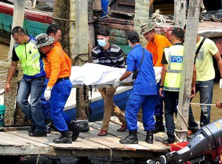 Rescuers carry a body recovered from a capsized boat carrying illegal migrants at a jetty in Hutan Melintang in Malaysia