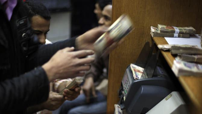 FILE - In this Wednesday, Jan. 2, 2013 file photo, Egyptians count money at a currency exchange office in downtown Cairo, Egypt. Egypt's foreign currency reserves fell nearly 10 percent in a single month in January, according to figures released by the central bank Tuesday, Feb. 5, 2013, that provided stark new evidence of a dangerous deterioration in the economy amid political turmoil on the streets. (AP Photo/Khalil Hamra, File)