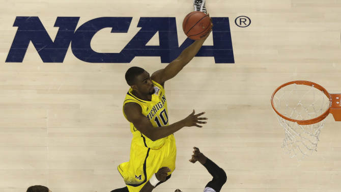 Michigan guard Tim Hardaway Jr. (10) heads to the hoop as Louisville center Gorgui Dieng (10) defends during the second half of the NCAA Final Four tournament college basketball championship game Monday, April 8, 2013, in Atlanta. (AP Photo/David J. Phillip)