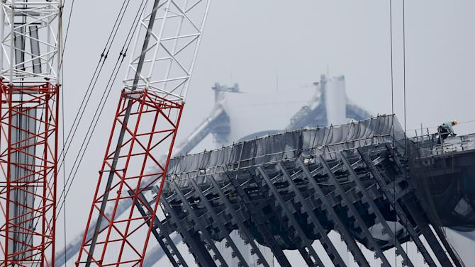 A man works on a top of a structure at a construction site in Tokyo