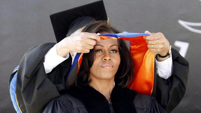 First lady Michelle Obama is hooded as she receives an honorary degree during the Oregon State University graduation ceremony in Corvallis, Ore., Sunday June 17, 2012. The first lady delivered the commencement address at Oregon State University, the school where her brother serves as head basketball coach. (AP Photo/Don Ryan)