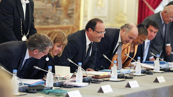 French President Francois Hollande, center, and government members, sit, at the start of a government seminar held at the Elysee Palace in Paris, Monday Aug. 19, 2013. From left: education minister Vincent Peillon, businesswoman Anne Lauvergeon, Francois Hollande, foreign minister Laurent Fabius, justice minister Christiane Taubira, interior minister Manuel Valls and employment minister Michel Sapin.(AP Photo/Remy de la Mauviniere/Pool)