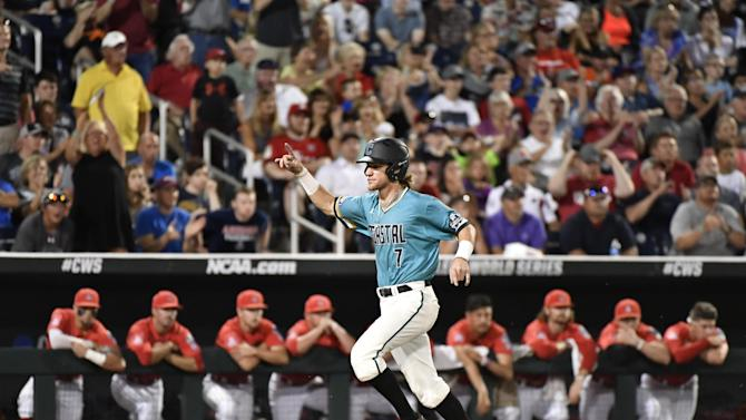 Coastal Carolina's Zach Remillard celebrates scoring on a G.K. Young two-run single in the  eighth inning in Game 2 of the NCAA Men's College World Series finals baseball game in Omaha, Neb., Tuesday, June 28, 2016. Young was out at second base. (AP Photo/Ted Kirk)